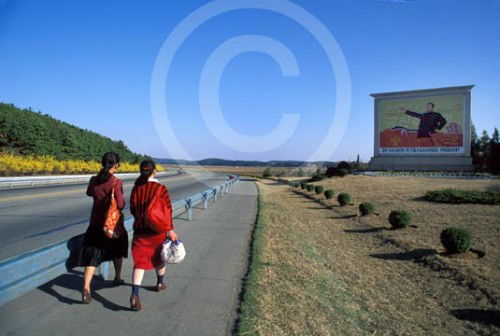 Photo of a North Korean highway with a propaganda billboard