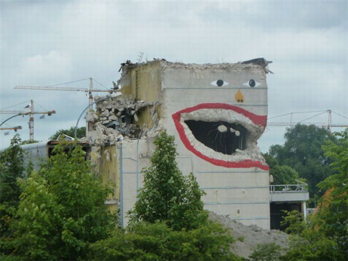 Photo of street art face on bombed building