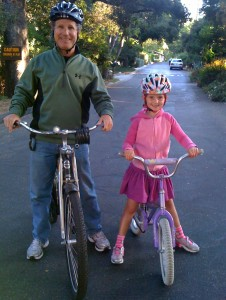 Photo of a father and daughter riding bikes