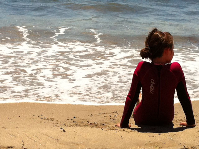 Photo of my daughter at the beach in her wetsuit